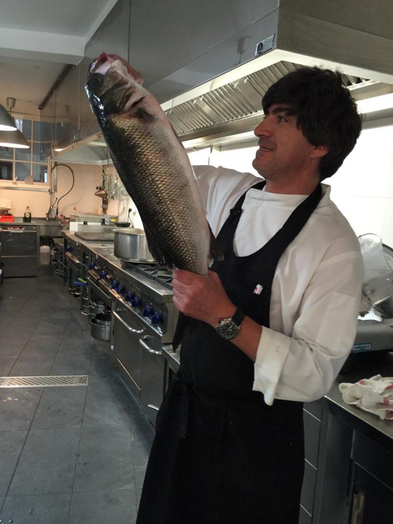 Juan Manuel de la Cruz con peixes dos que prepara no seu restaurante